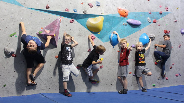 kids lined up at a climbing wall in leeds