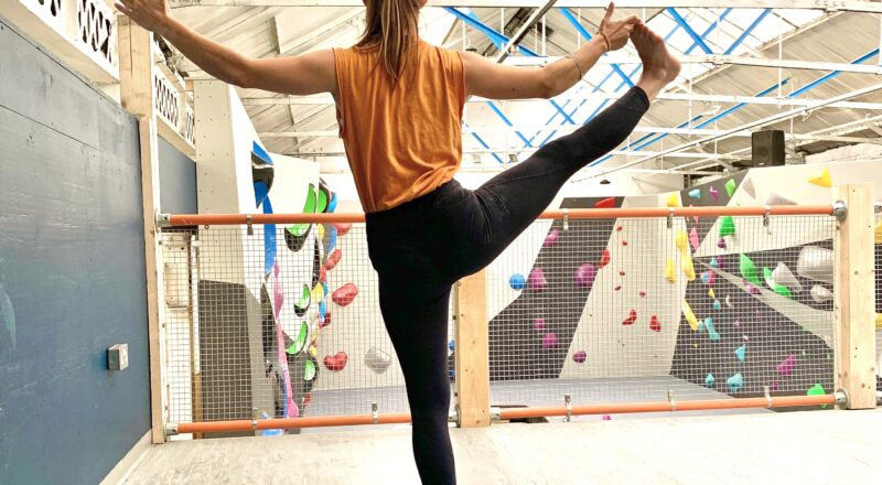 yoga posture in front of climbing wall