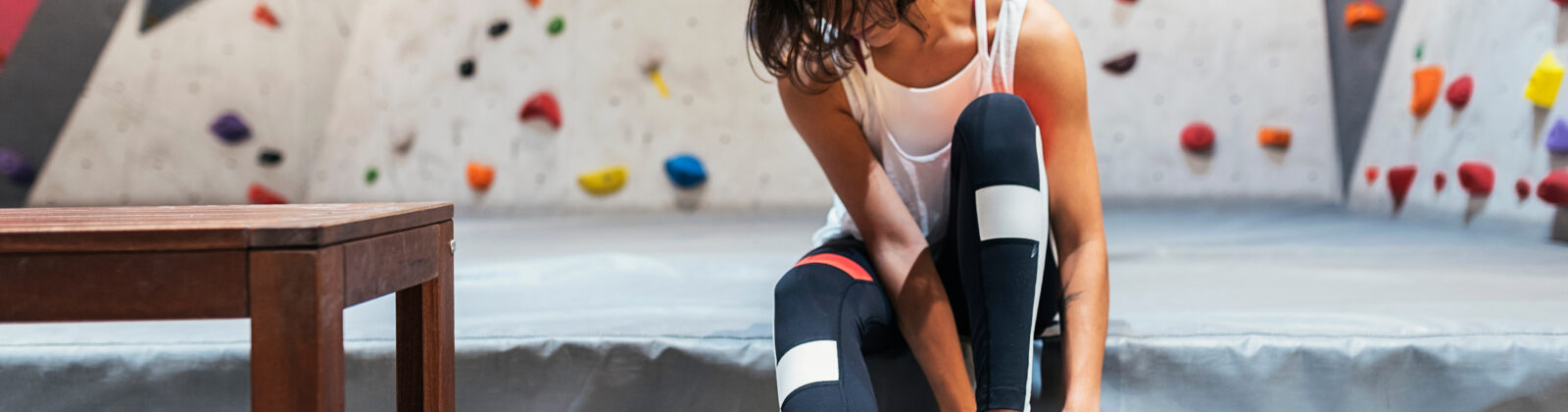 woman putting on climbing shoes